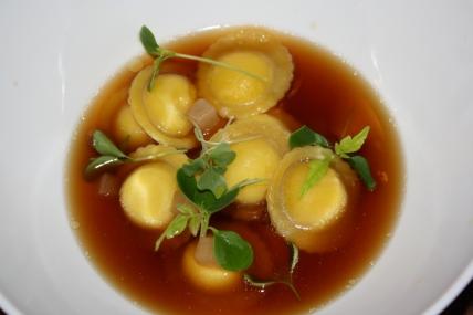Ravioli ripieni di parmigiano reggiano e foie gras con brodo di manzo profumato all'orientale.